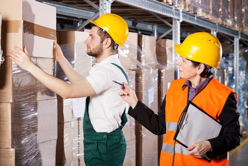 Manager met arbeider in pakhuis stock afbeelding