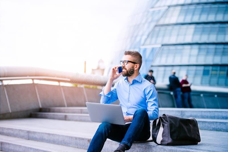 Manager met laptop en slimme telefoon, het Stadhuis van Londen royalty-vrije stock foto