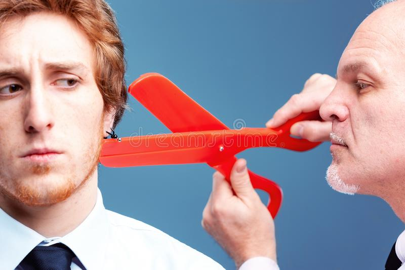 Manager oder Chef, die sich vorbereiten, weg von einem Ohrring zu schnippeln stockfotos