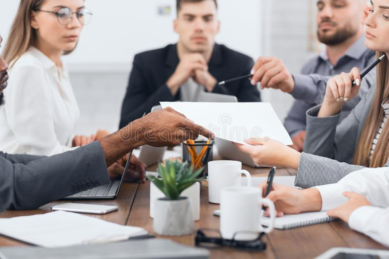 Manager passing documents to his colleagues at meeting stock photo
