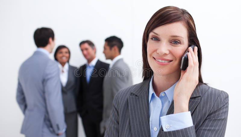 Download Manager On Phone With Her Team In The Background Stock Photo - Image: 12025432