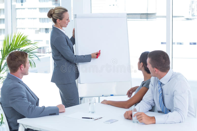 Manager presenting whiteboard to his colleagues royalty free stock photos