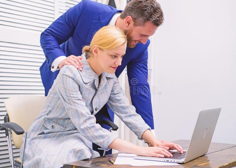 Manager putting his hand on the shoulder of his secretary, at the office. Bullying at work. Boss or manager molesting stock images