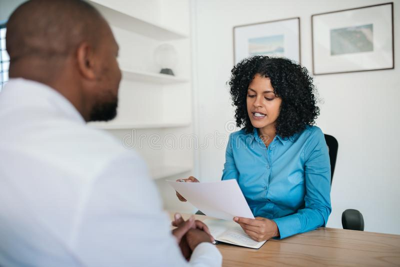 Manager reading a resume during an interview in her office. Manager reading a resume during an interview with a potential new employee at her desk in of an royalty free stock image