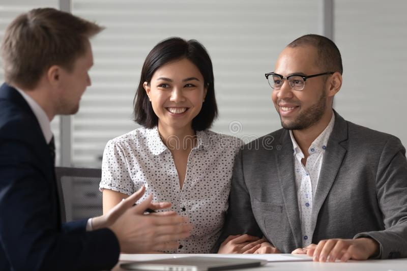 Manager realtor banker consulting happy diverse young couple at meeting stock photography