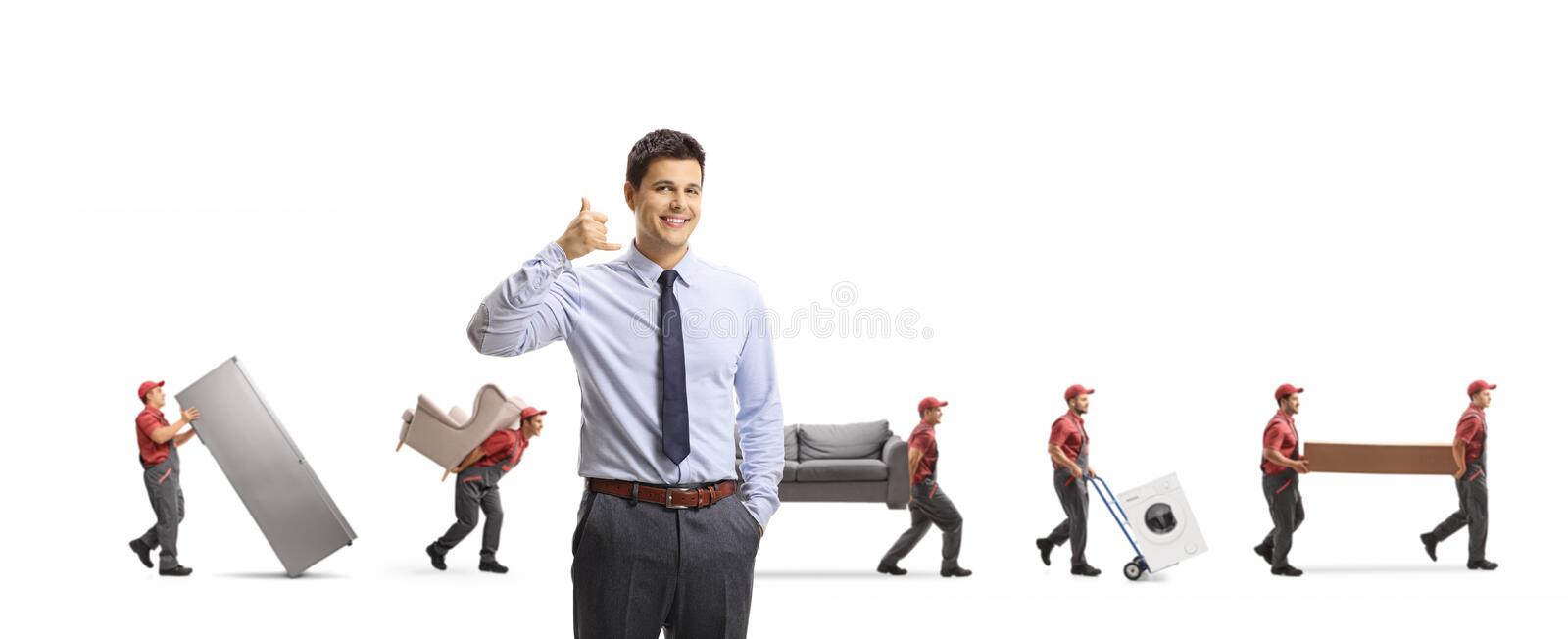 Manager of a removal company gesturing call us sign and workers carrying furniture and appliences royalty free stock photo