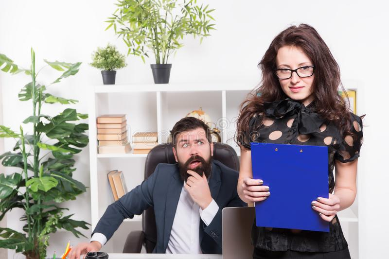 Manager responsible for managing office. Sensual office manager with boss on background. Project manager with sexy look. Adorable secretary holding folder in stock image