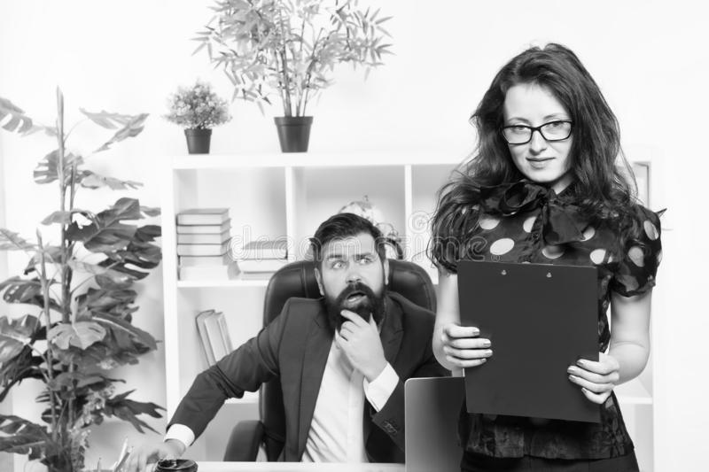 Manager responsible for managing office. Sensual office manager with boss on background. Project manager with sexy look. Adorable secretary holding folder in royalty free stock images