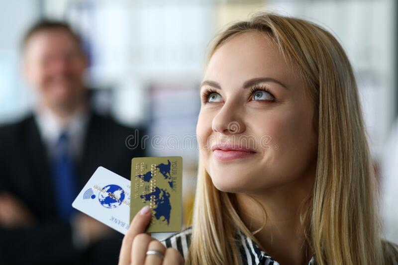 Manager restores solvency company or enterprise. Specialist is proud her achievements, girl is holding golden bank cards in her hands. Assistance to top royalty free stock photography