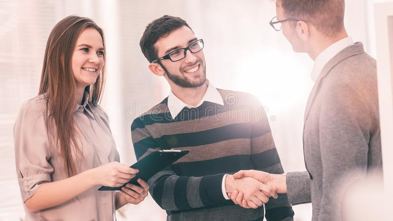 Manager shakes hands with the employee in a workplace in a modern office royalty free stock photography