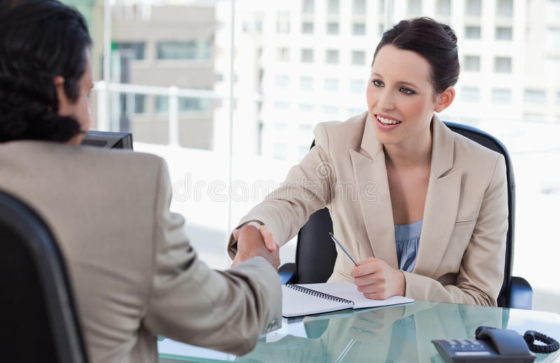 Manager shaking the hand of a male applicant. In her office stock photos