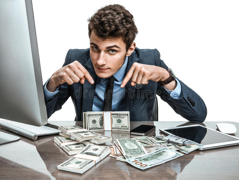 Manager showing his earnings, profit, income, gain, benefit, margin. Modern businessman at his desk with computer and a lot of money royalty free stock image