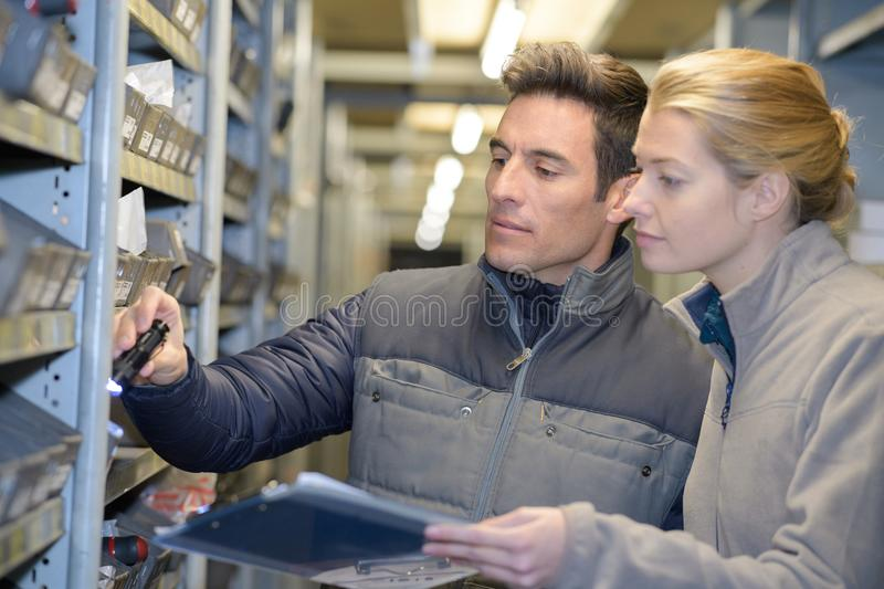 Manager showing shelves to workers in warehouse royalty free stock photos