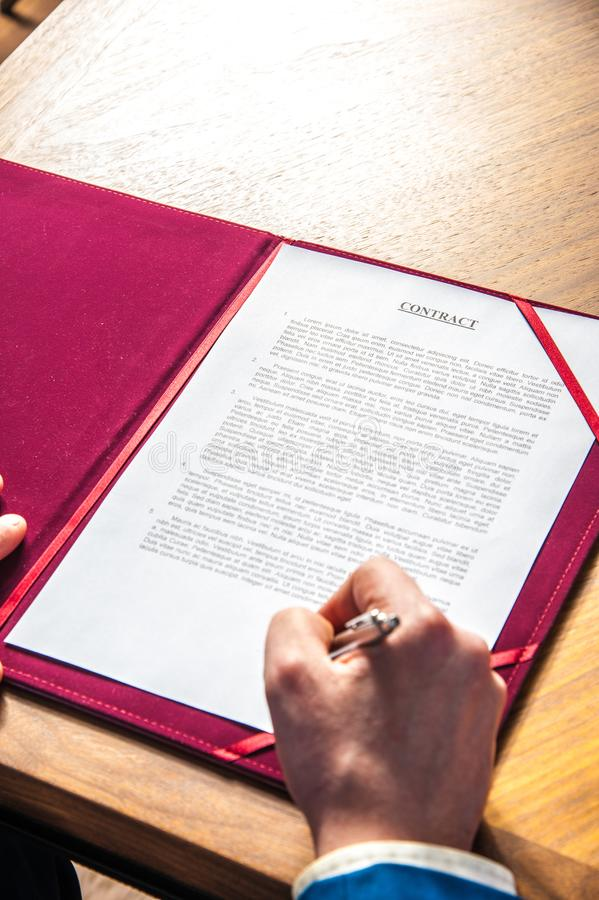 The manager signs the official contract on the parties` agreement. A manager signs the official contract on the parties` agreement in office on the desk royalty free stock photos