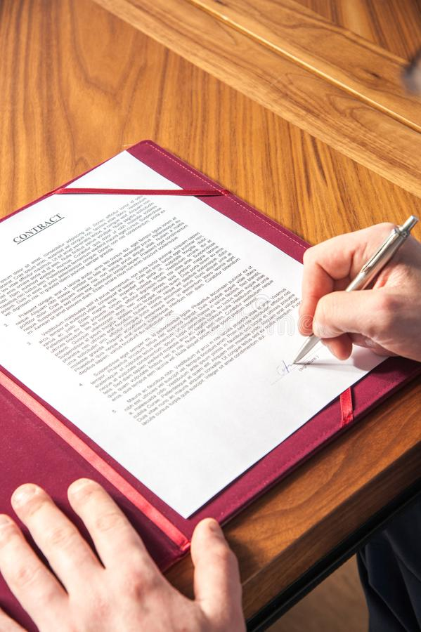 The manager signs the official contract on the parties` agreement. A manager signs the official contract on the parties` agreement in office on the desk royalty free stock image