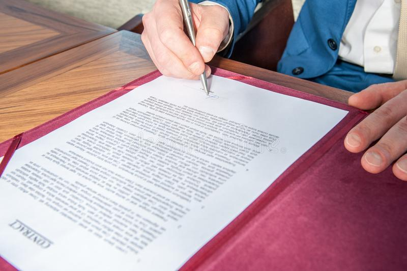 The manager signs the official contract on the parties` agreement. A manager signs the official contract on the parties` agreement in office on the desk stock photos