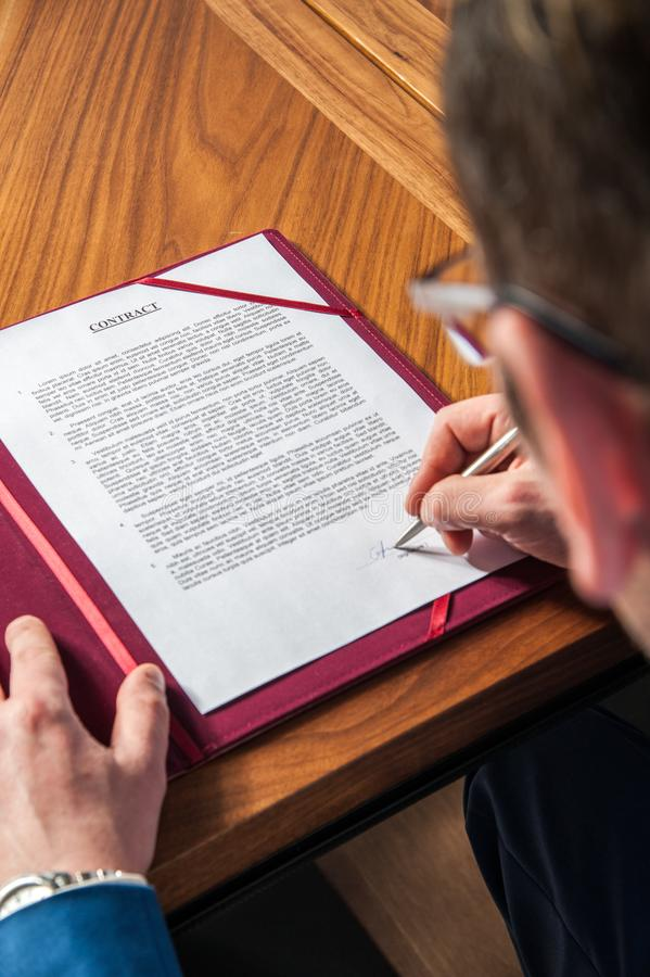 The manager signs the official contract on the parties` agreement. A manager signs the official contract on the parties` agreement in office on the desk royalty free stock photo