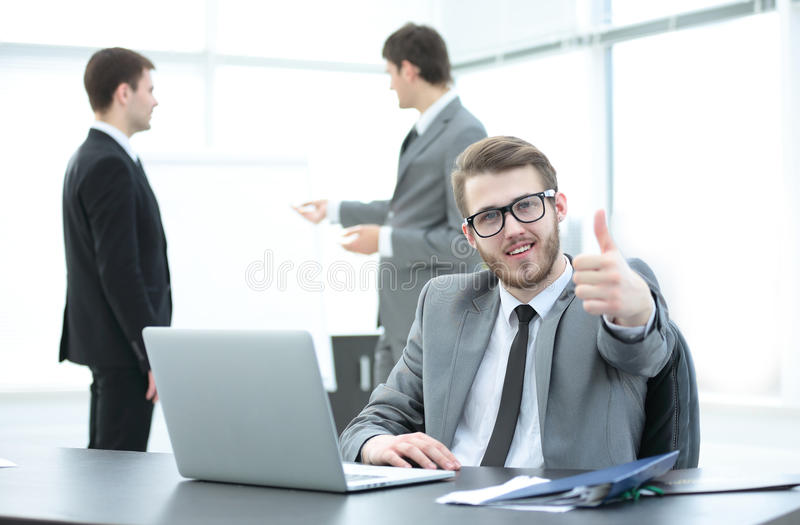 Manager sits at a Desk with an open laptop and showing thumbs up. In the foreground is a successful Manager sits at a Desk before an open laptop and showing stock photography