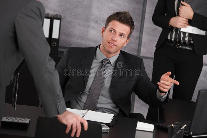 Download Manager Sitting At Desk, Teaching Employee Stock Photo - Image: 25641998