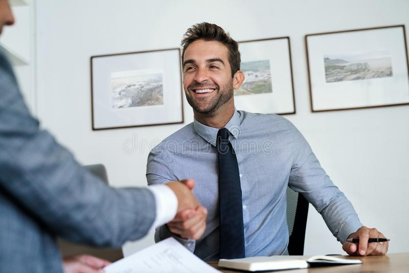Manager sitting at his desk shaking hands with an employee stock photos