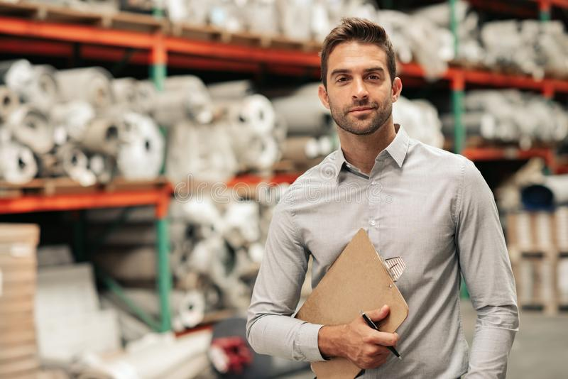 Manager standing with an inventory clipboard on a warehouse floor royalty free stock photos
