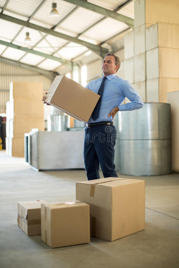 Manager suffering from back pain while holding heavy box. In factory stock photography