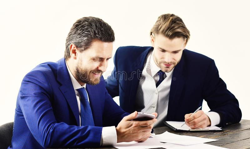Manager surfs internet. Management, leadership concept. CEO gives instructions to office worker. Business partners work with documents and smartphone. Busy stock photo