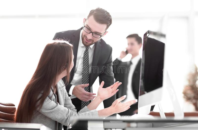 Manager talking with an employee. Standing near the desktop in the office stock photo