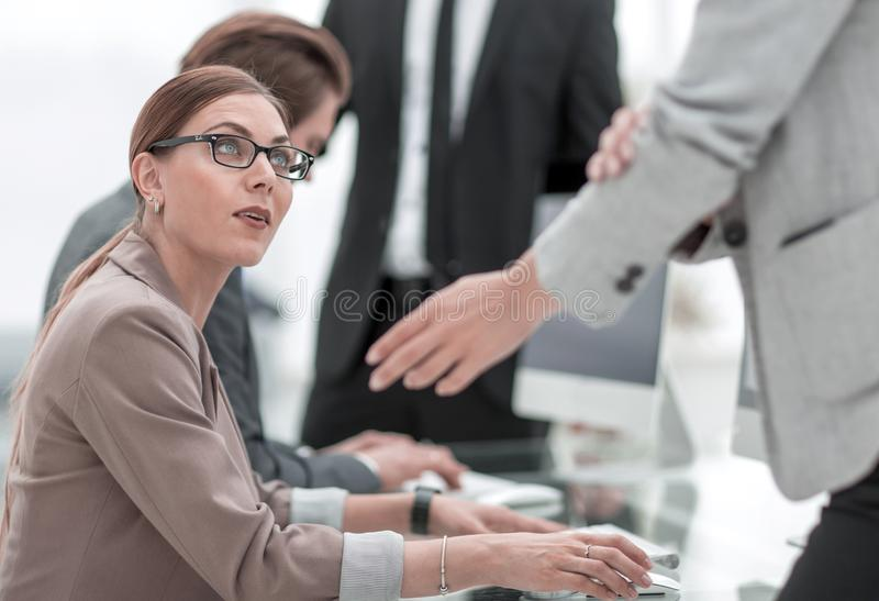 Manager talking with employees near the desktop royalty free stock image