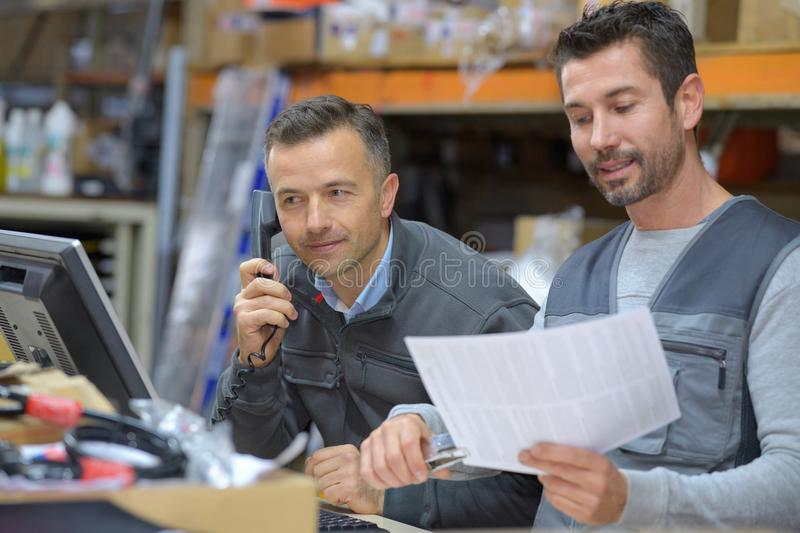 Manager talking on phone next to worker in warehouse royalty free stock images