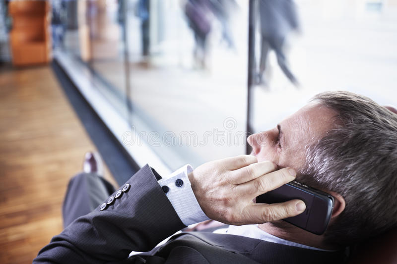 Manager talking on phone, people in background. royalty free stock photo