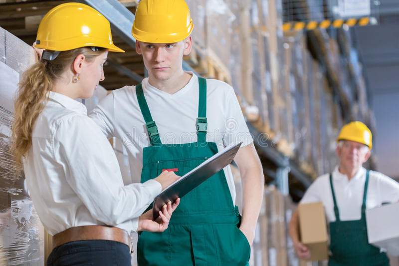Manager talking with storage worker stock image