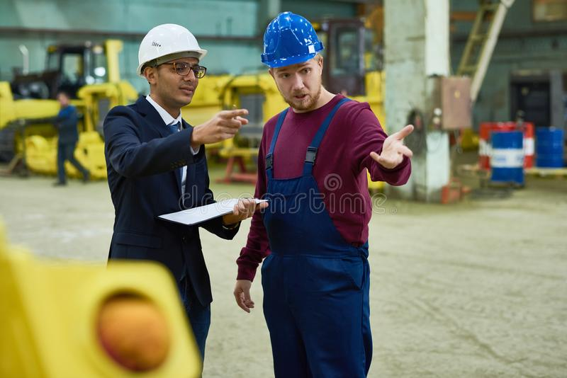 Manager Talking to Workers at Plant. Portrait of factory worker talking to Middle-Eastern manager in workshop of modern plant, copy space royalty free stock photo