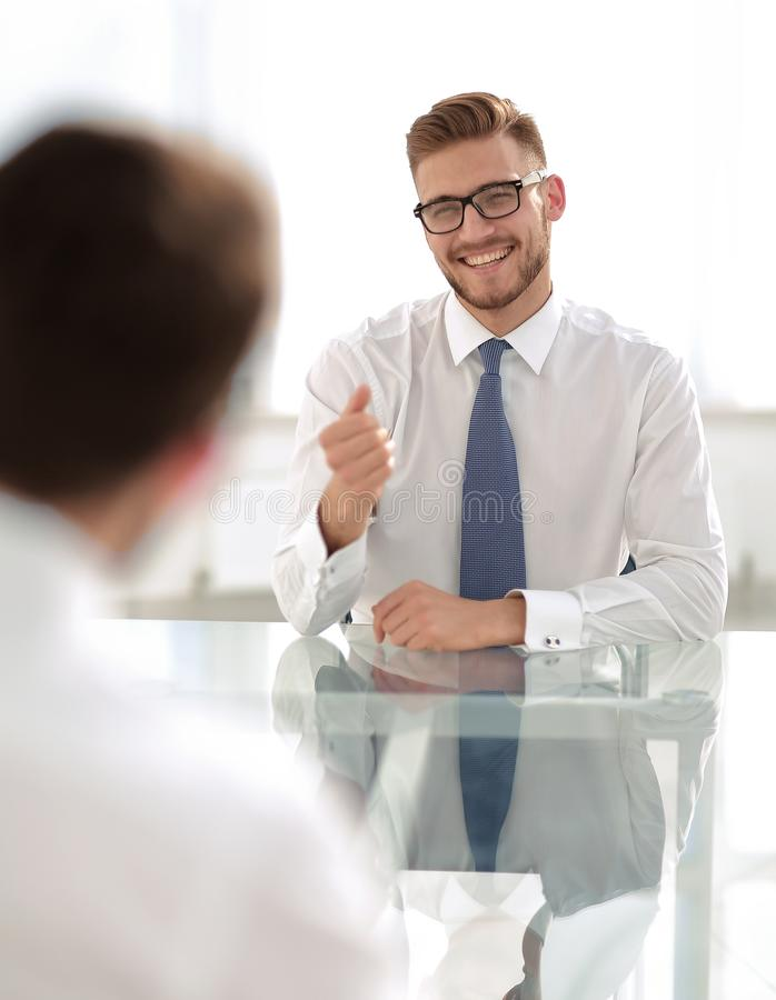 Manager talks to the employee sitting at his Desk royalty free stock photography