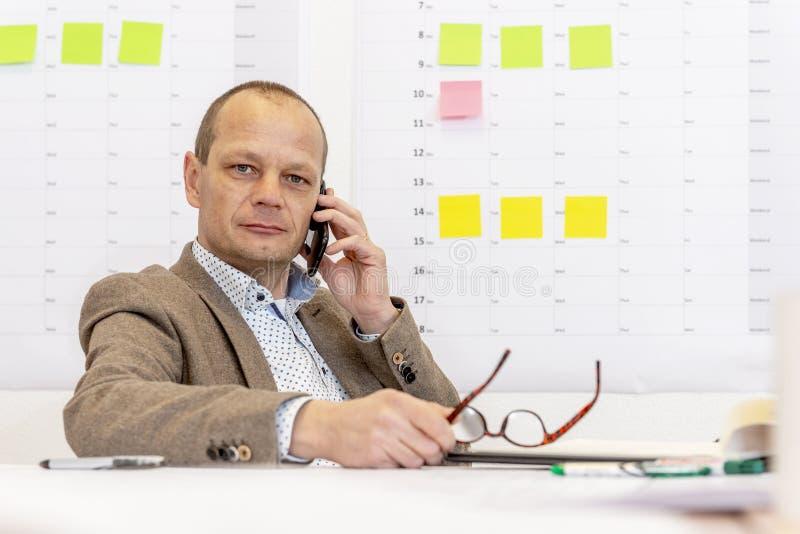 Manager am Telefon hinter einem Schreibtisch lizenzfreies stockbild