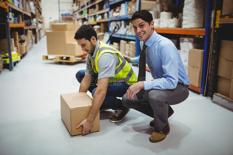 Manager training worker for health and safety measure. In a large warehouse stock photo