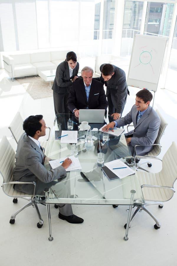 Manager und seine Kollegen, die an einem Computer arbeiten stockbilder