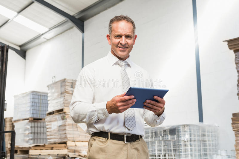 Manager using digital tablet in warehouse royalty free stock photo