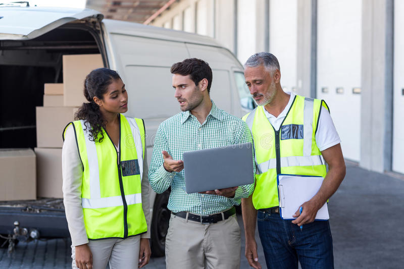Manager and warehouse workers discussing with laptop royalty free stock photography