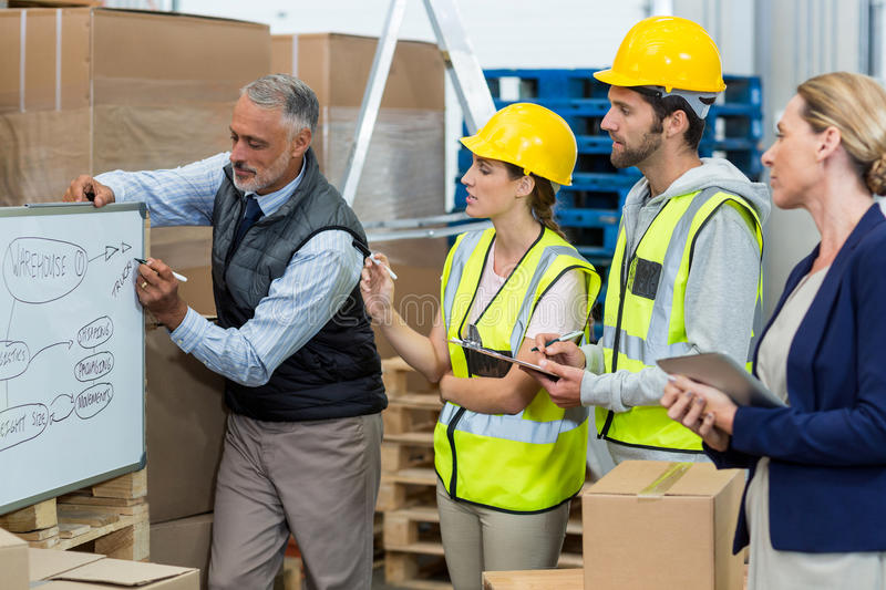 Manager and warehouse workers discussing over whiteboard stock image