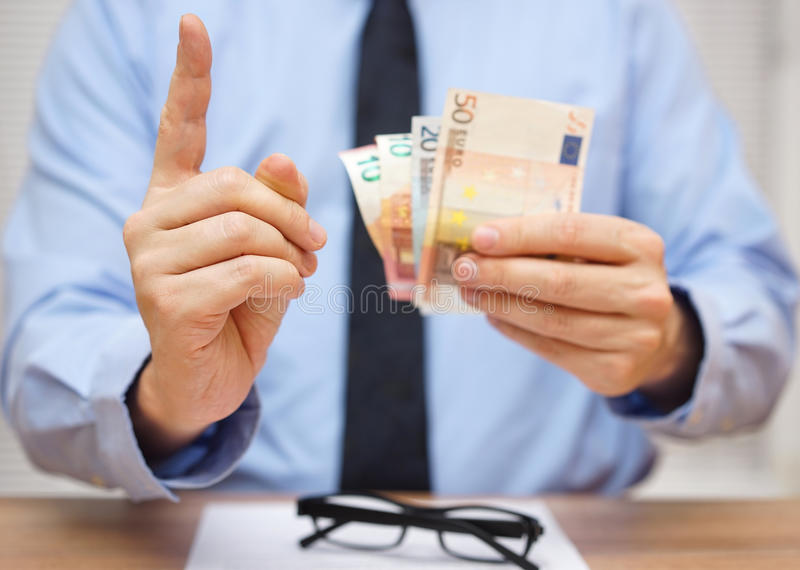 Manager warnt den Angestellten, während er ihm Geld gibt lizenzfreie stockbilder