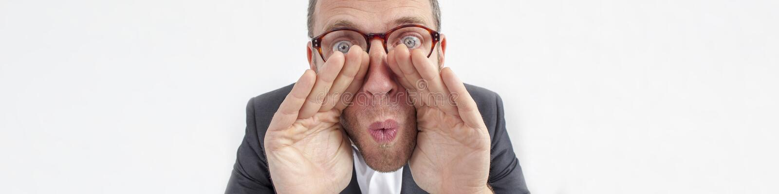 Manager whispering for management strategies with hands like loud-hailer. Expressive corporate man concept - excited middle age businessman whispering with hands stock images