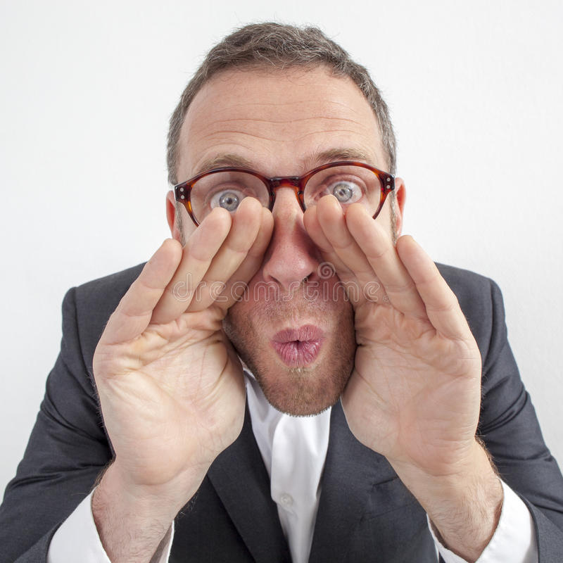 Manager whispering, shouting management strategies with hands like loud-hailer. Expressive corporate man concept - excited middle age businessman whispering with stock photography
