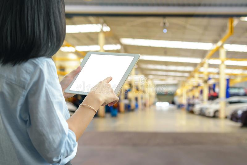 Manager woman using a tablet pc with blur of auto repair service at garage royalty free stock photo