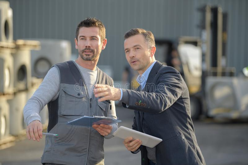 Manager with worker discussing over clipboard in industry stock photo