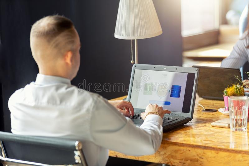 Manager works at a laptop in the office. The man sits with his back in the frame. in front of him is his laptop. concept of office work and workplace royalty free stock image