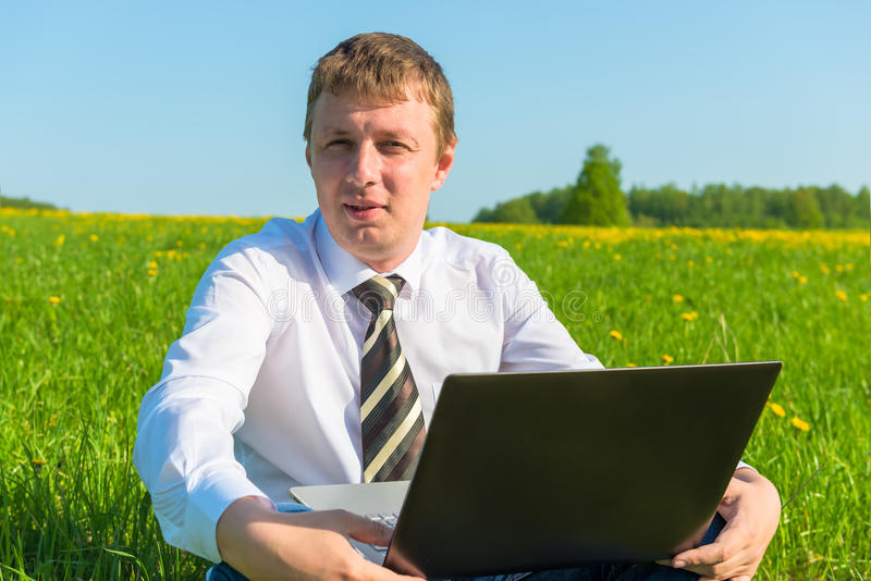 Manager works on nature. With laptop stock photography