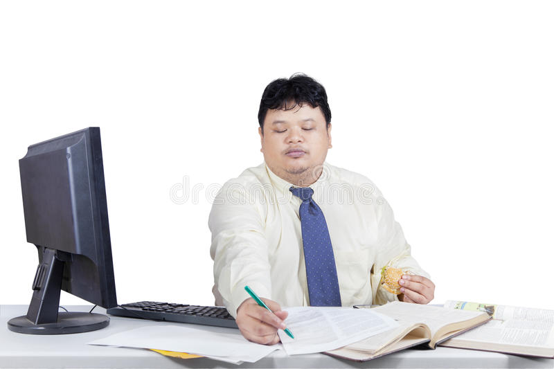 Manager writes on paper while eating burger. Portrait of overweight manager working on table while eating burger and write on paper stock photos