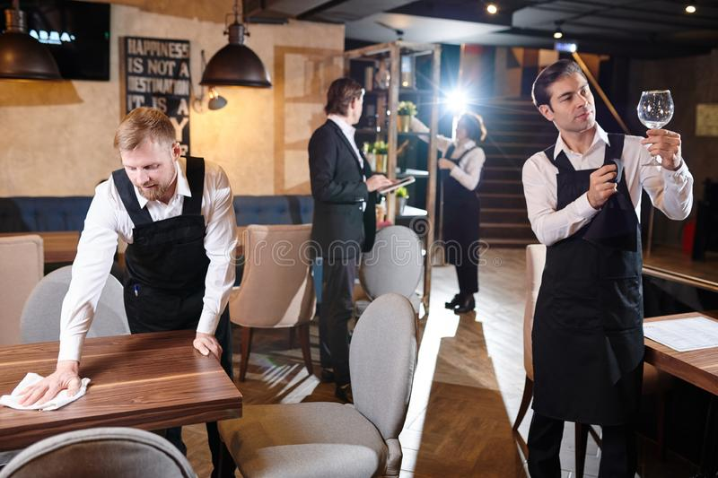 Preparing restaurant for opening. Manager and young waiters working together and preparing restaurant for opening: bearded men wiping wooden table, handsome stock image