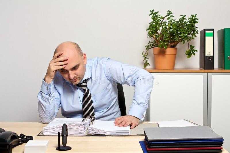 Managerblicke demotiviert in seinen Dateien lizenzfreie stockfotos